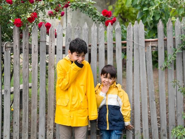 Dzieci są szczęśliwe i mają na sobie płaszcze przeciwdeszczowe