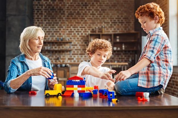 Dzieci są tęczą życia. uważna babcia patrząc na swoje wnuki, siedząc przy stole i bawiąc się zestawem kolorowych plastikowych zabawek