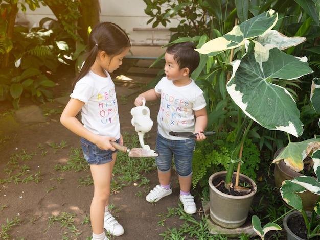 Dzieci są w ogrodzie, podlewając rośliny