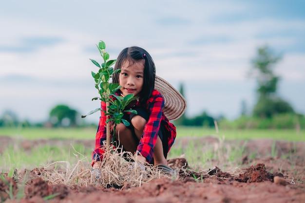 Dzieci sadzą drzewo na ziemi i rozmytym tle przyrody
