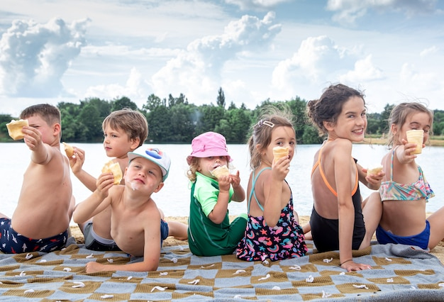 Dzieci siedzą na kocu nad rzeką i odpoczywają po kąpieli.