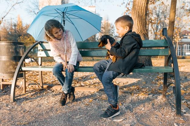 Dzieci siedzą na ławce z jamnikiem psa
