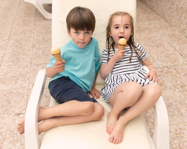 Dzieci siedzą na łóżku w słońcu i jedzą lody