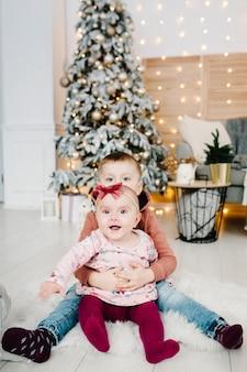 Dzieci siedzą na podłodze w pobliżu choinki. wesołych świąt. boże narodzenie urządzone wnętrze. pojęcie rodzinnych wakacji zimowych.