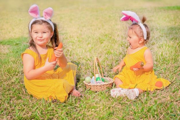 Dzieci siedzą na polanie w uszach zajączka wielkanocnego. dziewczyny gryzą marchewki i bawią się koszykiem pisanek
