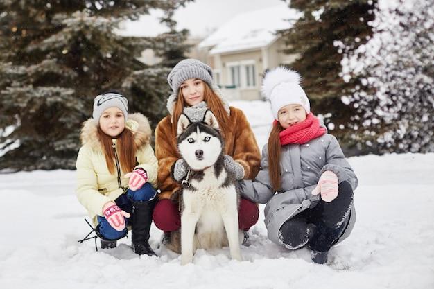 Dzieci siedzą na śniegu i głaskają psa husky. dzieci wychodzą i bawią się z psem husky w zimie. spaceruj po parku zimą, radość i zabawa, pies husky o niebieskich oczach. , gru