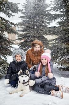 Dzieci siedzą na śniegu i głaskają psa husky. dzieci wychodzą i bawią się z psem husky w zimie