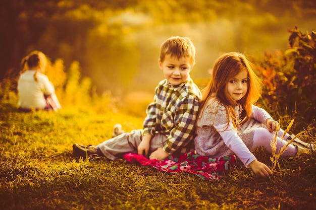 Dzieci siedzą obok siebie na szkockiej kraty