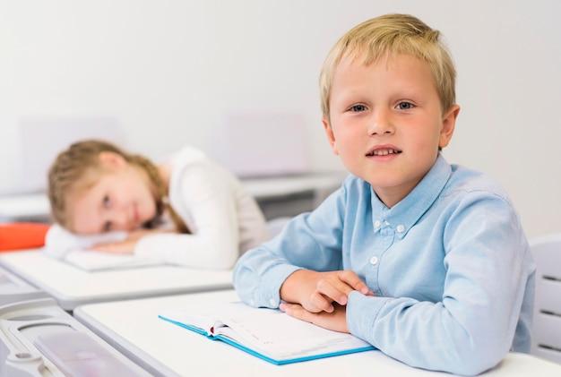 Dzieci siedzą przy biurku w klasie