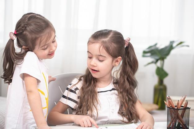 Dzieci siedzą przy stole i odrabiają lekcje