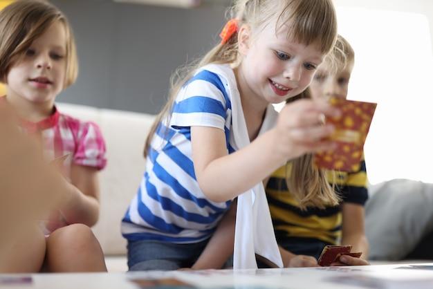 Dzieci siedzą przy stole jedna dziewczyna brzozy grając w karty i uśmiechając się.