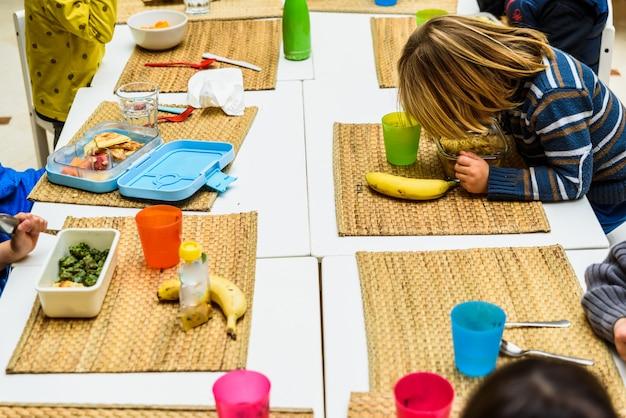 Dzieci siedzą przy stole w szkolnej stołówce, a nauczyciele podają im jedzenie.