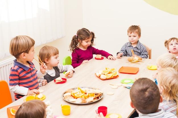 Dzieci siedzą przy stole z obiadem i jedzą owoce i ciasta