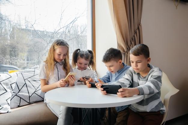 Dzieci siedzą przy stoliku w kawiarni i razem grają w telefony komórkowe. nowoczesna rozrywka.