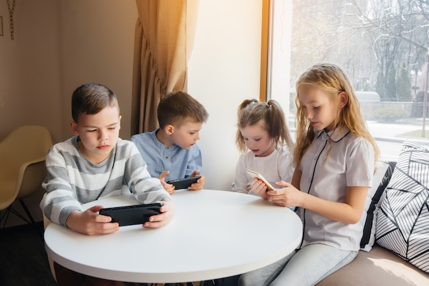 Dzieci siedzą przy stoliku w kawiarni i razem grają w telefony komórkowe.