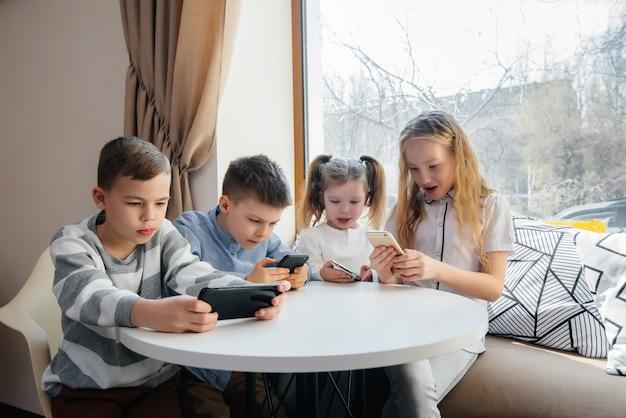 Dzieci siedzą przy stoliku w kawiarni i wspólnie bawią się telefonami komórkowymi
