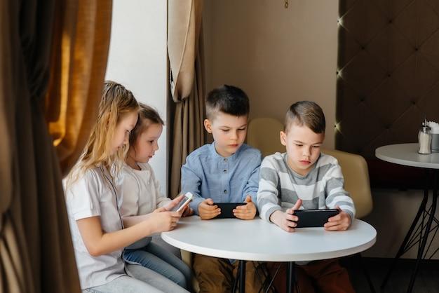 Dzieci siedzą przy stoliku w kawiarni i wspólnie grają w telefony komórkowe. nowoczesna rozrywka.