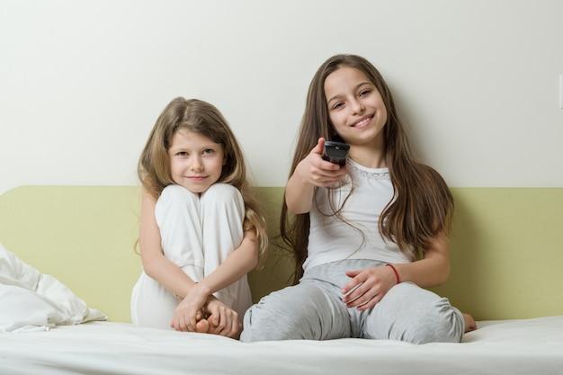 Dzieci siedzą w domu na łóżku i oglądają telewizję