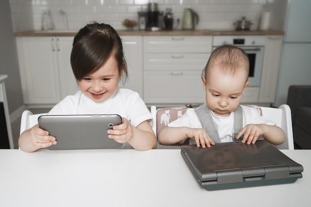 Dzieci siedzą z gadżetami. edukacja na odległość dla dzieci. dziewczyna siedzi z tabletem i laptopem. nowoczesne cyfrowe dzieciństwo. dzieci często oglądają bajki