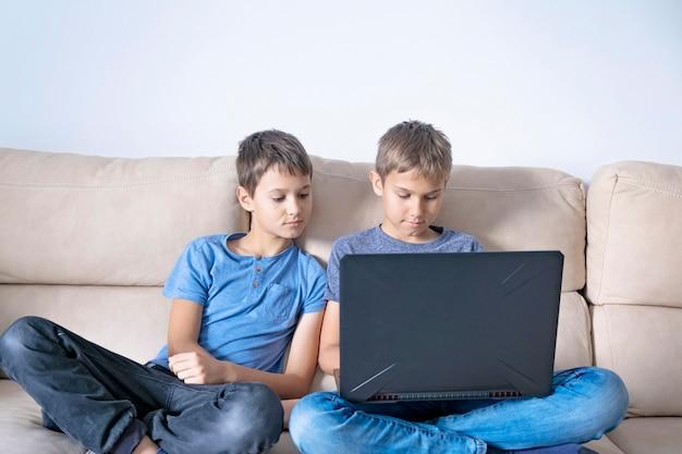 Dzieci siedzą z laptopem i odrabiają lekcje lub oglądają wideo w domu