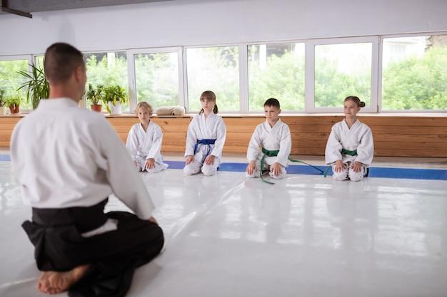 Dzieci siedzące przy oknie i uważnie słuchające swojego trenera aikido