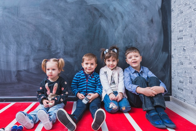 Dzieci siedzące w pobliżu ściany