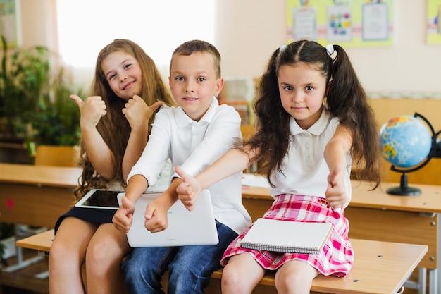 Dzieci siedzi na szkolnym biurku gesturing