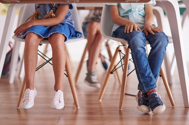 Dzieci siedziały przy ławkach w szkole