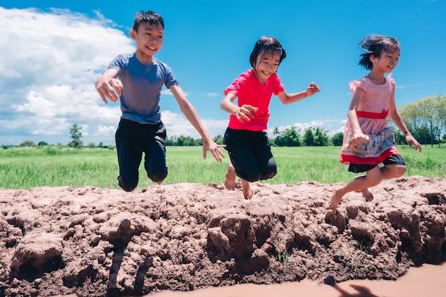 Dzieci skaczą do wody i rozpryskują się podczas zabawy na wsi na tle błękitnego nieba i pola ryżowego