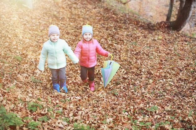 Dzieci spacerują po jesiennym parku jesienią