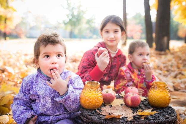 Dzieci spacerują po parku i jedzą śniadanie