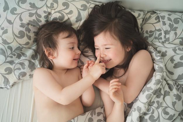 Dzieci śpią w łóżku dwie siostry oddają się przed snem brat i siostra nie śpią