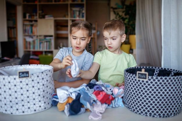 Dzieci sprzątają pokój, sortują skarpetki i układają je w osobiste kosze. codzienna rutyna z dobrą zabawą