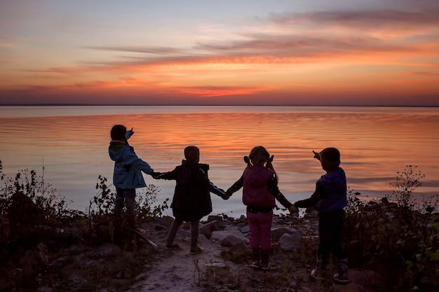 Dzieci stoją razem trzymając się za ręce i patrzą na zachód słońca niesamowite sylwetki aktywny rodzinny weekend