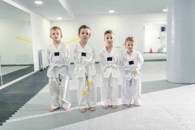 Dzieci stoją w dobokach z rękami za plecami i czekają na rozpoczęcie zajęć taekwondo.
