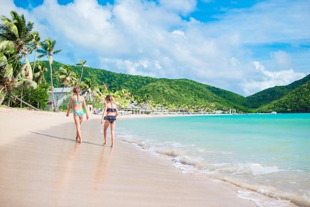 Dzieci świetnie się bawią na tropikalnej plaży podczas letnich wakacji. małe dziewczynki biegają w płytkiej wodzie