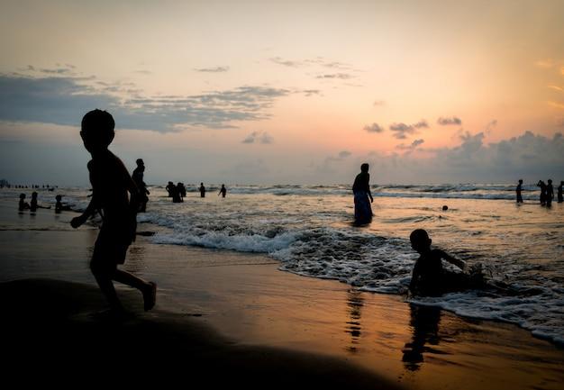 Dzieci sylwetki o szczęśliwy czas na morzu plaży w pobliżu zachodu słońca