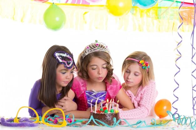Dzieci szczęśliwe dziewczyny dmuchanie tort urodzinowy