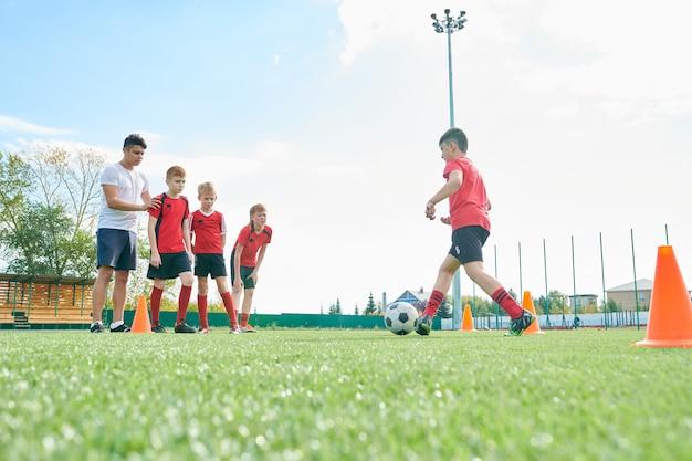 Dzieci trenujące w szkole futbolu