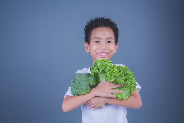 Dzieci trzyma warzywa na szarym tle.