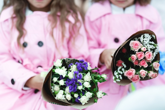 Dzieci trzymają różowe i fioletowe bukiety