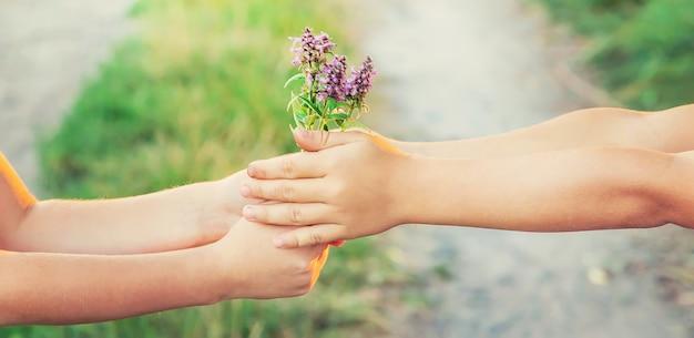 Dzieci trzymają się za ręce razem z kwiatami. selektywne ustawianie ostrości.