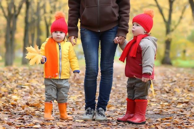 Dzieci trzymające się za ręce rodzica spacerują w jesiennych liściach parku