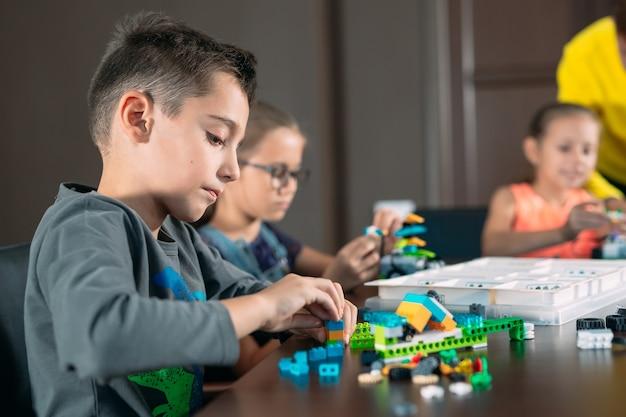 Dzieci tworzą roboty z nauczycielem.