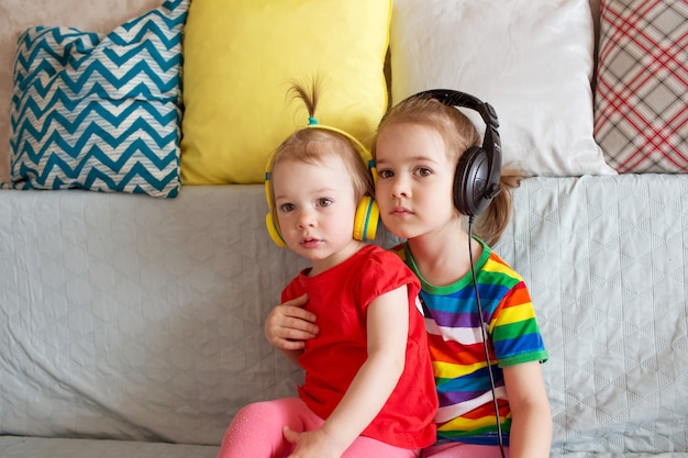 Dzieci uczą się angielskiego ze słuchawkami. dwie dziewczyny słuchają muzyki na słuchawkach