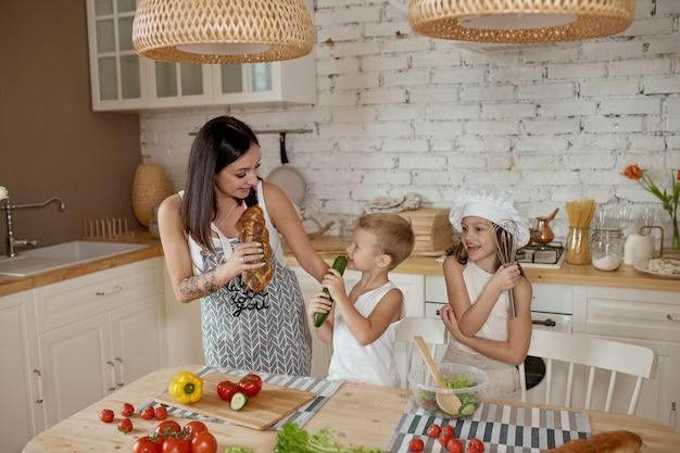 Dzieci uczą się, jak przygotować sałatkę w kuchni. rodzinny dzień wolny, obiad własnymi rękami. mama i młodzi kucharze
