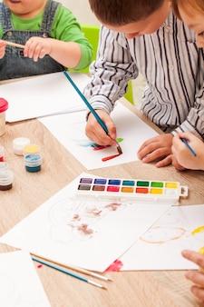 Dzieci uczą się malować pędzlem i akwarelami na papierze w przedszkolu