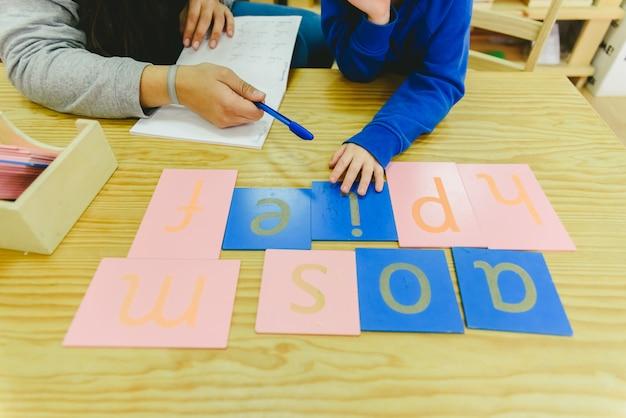 Dzieci uczące się pisać w dziedzinie czytania i pisania w szkole montessori.