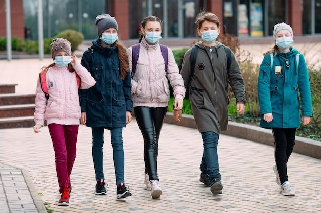 Dzieci uczniowie w maskach medycznych opuszczają szkołę.