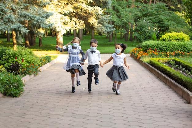 Dzieci uczniowie w mundurkach szkolnych chłopiec blondynka i brunetka biegną